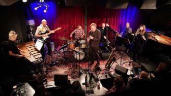 """Bandet """"Mining"""" från vänster till höger: Josefin Runsteen (fiol o marimba), David Stackenäs (gitarr), Jon Fält (trummor), Fredrik Ljungkvist (sax o klarinett), Dan Berglund (bas), Mattias Risberg (klaviaturer) och Jennie Abrahamsson (sång)."""