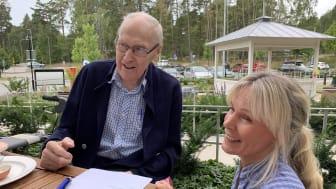 """""""Man lär sig hela livet, nu får vi sitta ute och prova de här pajerna, det är toppen. Annars håller jag på att lära mig mer om datorer just nu, säger Sten Säflund, 96 år"""". Här tillsammans med Maria Eriksson från Karlsundsgården."""