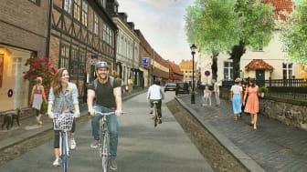Visionsbild över Norra Storgatan med bredare trottoarer, historisk belysningsstolpe, klätterrosor och cyklister i fokus.