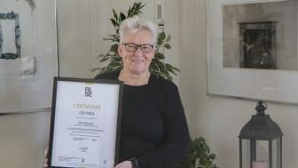 Väsbyhems kvalitets- och miljösamordnare Anette J:son Skogh håller stolt upp certifikatet för Väsbyhems kvalitetscertifiering enligt ISO 9001