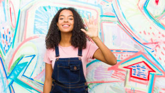 A young Black woman stands against a patterned background. She is smiling and holding up her hand with her palm flat in the symbol for International Women's Day 2021. Royalty-free stock photo ID: 1549871621