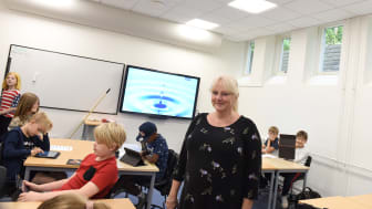 Head of School Jette Bonde Mikkelsen in one of the school's classrooms together with lively, happy children.
