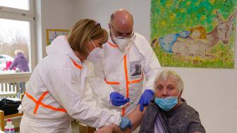 Angela Komossa und Horst Sehner vom Zentralbereich Gesundheit und Therapie (von links) der Hephata Diakonie impfen Edeltraut Stritt (84), Bewohnerin im Wohnverbund Alter Gutshof.