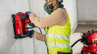 Mann slisser spor i betong til rør eller kabler. Maskin koblet til støvsuger for støvfri slissing.