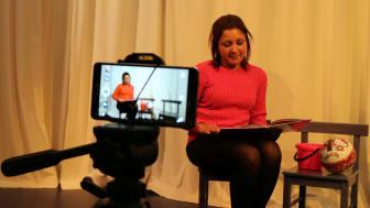 Venetia Lärlund filmas när hon läser en saga på språket lovari i projektet Romska sagor på Lunds stadsbibliotek. Foto: Tove Eriksson