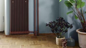 En högst ordinär radiator inklusive rör hela vägen upp mot taket målade i Anis 681. Tillsammans med väggen i kulören Skilla 779 skapas ett industriellt och högaktuellt uttryck.