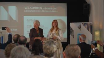 """Norges Banks Kristin Gulbrandsen overrekker den første av den nye 20-kronen """"Norgespulsen"""" til kunststudent Kjersti M. Austdal som har stått for designet."""