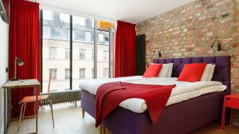 Hotellrum med glas- och tegelvägg