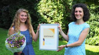 Christina Schuh (li.) erhält von Serap Meral (re.), Account Manager Clinics von Cochlear Deutschland, das Cochlear™ Graeme Clark Stipendium 2021