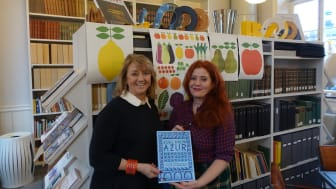 Ewa Kumlin och Lotta Kühlhorn i biblioteket på Svensk Form, med vinnarboken AZUR framför de prisvinnande affischer som Lotta har gjort för Akademibokhandeln.