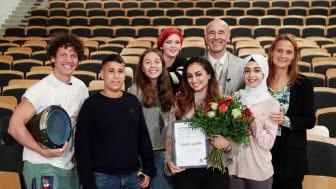 Årets nya lärare Fabiola Lahdo med elever, programledare Mark Levengood, prisutdelare Nassim al Fakir och Anna Rastner, utbudschef UR. Foto: UR.