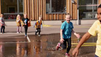 Glada barn på Västerstrandsskolan firar Generation Pep certifieringen ute på skolgården.