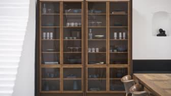 Ramel vitrinen har mørkere kontrastlister,  som sammen med de dybe, slanke lister giver møblet karakter. Hyldernes rytmiske forløb bidrager til den samlede oplevelse af et selvstændigt møbel.