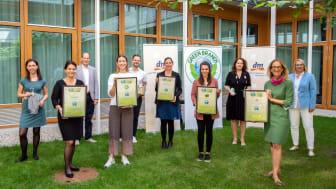 dm-Geschäftsführerin Kerstin Erbe (in Grün) mit den Kolleginnen und Kollegen der dm-Marken-Teams und Norbert Lux (graues Jacket) bei der Übergabe des GREEN BRANDS Gütesiegel.