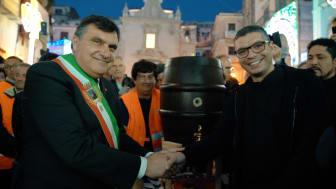 "Bürgermeister Roberto Perrotta zapft mit Padre Antonio das Fass ""Paolaner"" an."