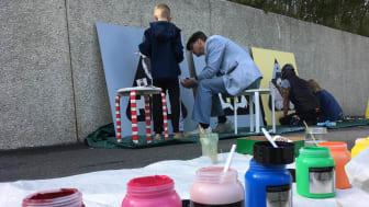 Gatukonstnären Paul Kuniholm, från USA, målar tillsammans med barnen i Öxnehaga.