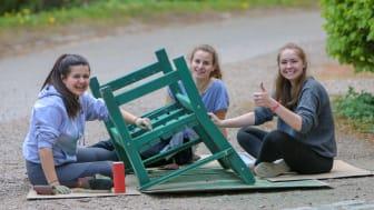 Schülerinnen streichen eine Bank
