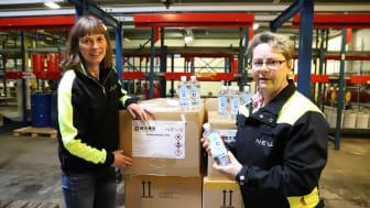 Ingrid Svensson och Kristin Lönngren från NEVS sätter på svenska etiketter på flaskorna.