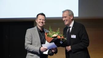 Formand for Torkil Holm priskomitéen Klaus Bock overrækker prisen til lektor Thomas Poulsen fra Aarhus Universitet (foto: Tom Jersø)