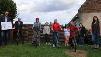 Thomas Blum, Christoph Metternich und Beate Schumacher von der Allianz freuen sich mit Josephine, Samantha und Elaine und den Mitarbeiterinnnen der Wohngruppe in Elz um Gruppenleiterin Stefanie Kück (von links) über die neuen Fahrräder.