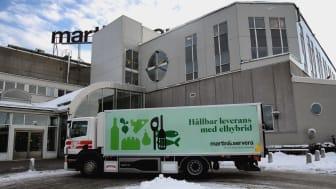 Den nya elhybridlastbilen utanför Martin & Serveras entré i Årsta