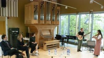 Musikstudenter i folkmusik spelar under mötet i Körsalen på Kungl. Musikhögskolan. Till vänster minister Matilda Ernkrans och hennes team.