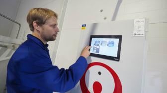 Andreas Bjørnøy, disiplinleder elektro og automasjon på Sjøtroll Kjerelva, viser et Magelis-styrepanel (HMI) på fiskeanlegget.