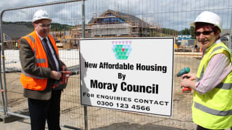 Cllrs McConachie (L) and Murdoch fixing signage at Dufftown housing development