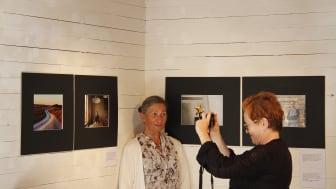 Iwona Hrynczenko från Burs bjöd spontant Tarkovskij på mat. Victoria Ivleva fotograferar henne framför porträttet i utställningen