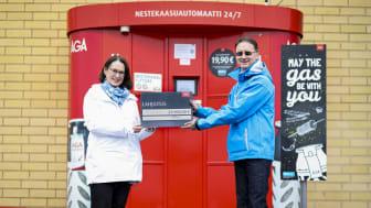 Annemi Usva-Vänttinen SOS-Lapsikylästä vastaanottaa 23 000 euron lahjashekin Linden edustajalta Johan Ginmanilta.