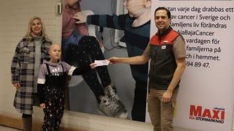 """10 åriga Alice som behandlas för cancer och hennes mamma Sophie tar emot det första presentkortet i projektet """"I Care AjaBajaCancer"""" av Roger Holgersson, butikschef ICA Maxi Stormarknad Häggvik."""