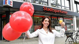 Filialleiterin Fadila Schluck begrüßt ihre Kunden zum 100. Geburtstag der Filiale am Stiglmaierplatz symbolisch mit einem Glas Sekt.