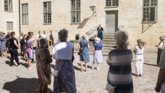 Det är en mindre skara personer som står på inre borggården, så som personal och leverantörer till utställningen. Glädjen är stor att äntligen få inviga en ny utställning på Kalmar Slott.