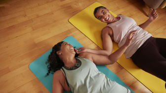 Two women on yoga mats enjoy exercise at home
