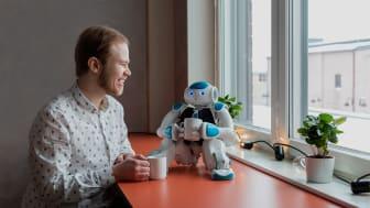 """Fredrik Löfgren från Dyno Robotics dricker kaffe med Nao-roboten """"David"""","""
