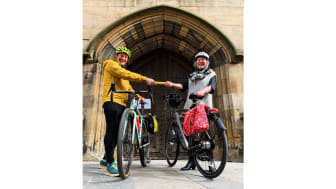 Northumbria University PhD researcher Shaun Cutler hands over the Cathedrals Cycle Route relay baton to The Revd Canon Clare MacLaren outside Newcastle Cathedral.
