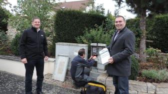Neben dem Bürgermeister Ronny Beck (re.) ist auch der zuständige Kommunalmanager der Bayernwerk Netz GmbH, Christian Ziegler (li.), bei der Installation von insgesamt fünf intelligenten Messsystemen in der Gemeinde Lauter vor Ort.