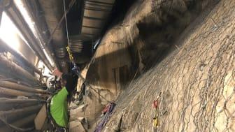 Reparbetare nere i kulverten kontrollerar  det monterade stålnätet.