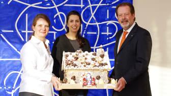 Frank Tepen, Personalchef der SIGNAL IDUNA, und Tanja Gerick (l.), L&D, überreichten ein mit einer Geldspende verbundenes Knusperhaus an Nora Gruschczyk (m.), Freundeskreis des Kinderpalliativzentrums Datteln.