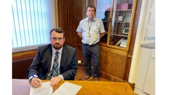 Council leader Eamonn O'Brien (seated) signs the joint GM letter on behalf of Bury, with (back) Cllr Alan Quinn.