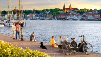 Flensburg: Relaxing on the wall of the marina with view of the old town with St. Mary's church