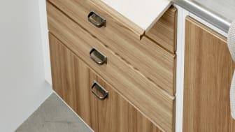 Træpladen, der trækkes ud, kan fungere som ekstra arbejdsplads eller spiseplads i det lille køkken.