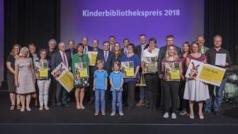 Gemeinsame Preisverleihung, doppelte Freude: Die fünf Gewinner-Büchereien des Kinderbibliothekspreises 2018 strahlen beim Siegerfoto im AURELIUM Lappersdorf mit dem diesjährigen Paul-Maar-Preisträger Jens Raschke (r.) um die Wette.
