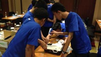 Para siswa sedang memperhatikan projektor Epson S200/X200 pada sesi assembly & disassembly