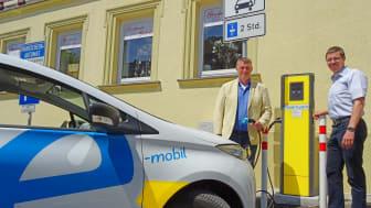 Zweiter Bürgermeister Hans-Josef Stich (l.) und Bayernwerk-Kommunalbetreuer Burkhard Butz nehmen die neue Stromtankstelle auf dem Marktplatz in Bad Staffelstein offiziell in Betrieb.