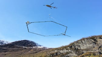 The antenna which registers the ground conditions hangs below the helicopter running along the area to be investigated