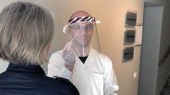 Coronatestningen sker med näs- eller halssvabbning, här läkarstudent Mikael Tyrberg.