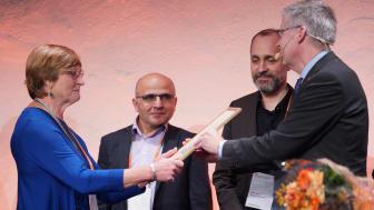 Eva Törn, ordförande i kulturnämnden i Värnamo tar emot diplomet av riksantikvarie Lars Amréus. I bakgrunden kommunarkitekt Behnam Sharo och Lars Alkner, kulturchef i Värnamo. Foto: Fredrik Streiffert(CCBY)