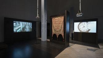 "Banner with text, ""8 Hours' Work! 8 Hours' Freedom! 8 Hours' Rest!"", ca. 1914. Revital Cohen, Tuur Van Balen, 75 Watt, 2013. Marcus Coates, Self Portrait as Time, 2016"