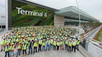 Airport staff and workers gather at Changi Airport's Terminal 4 facade to mark the completion of construction